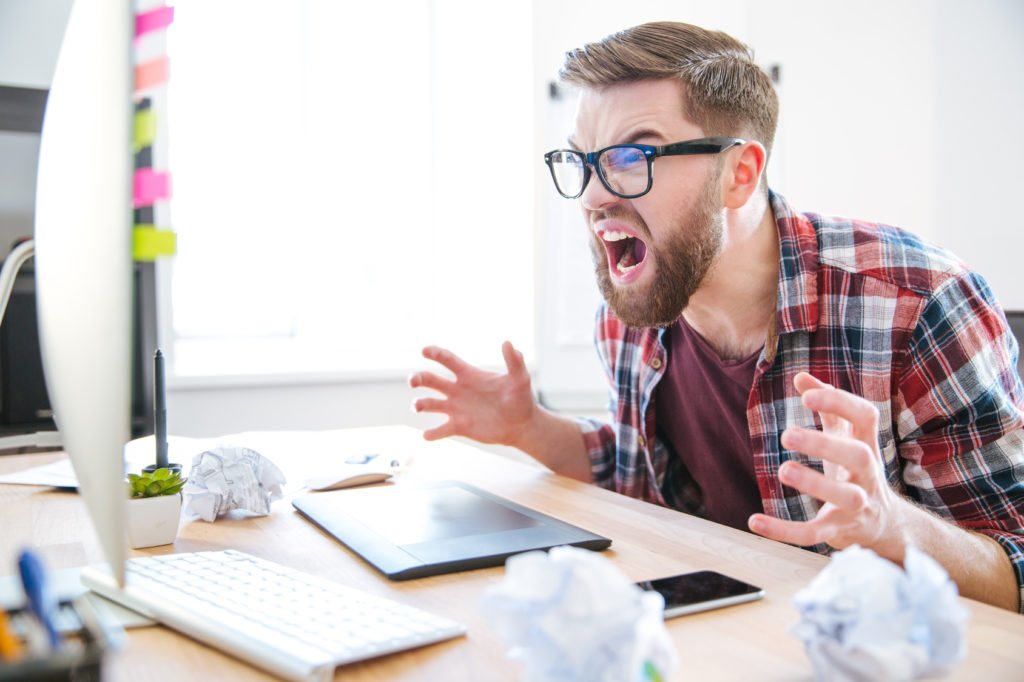 Mad agressive man designer looking at monitor and shouting