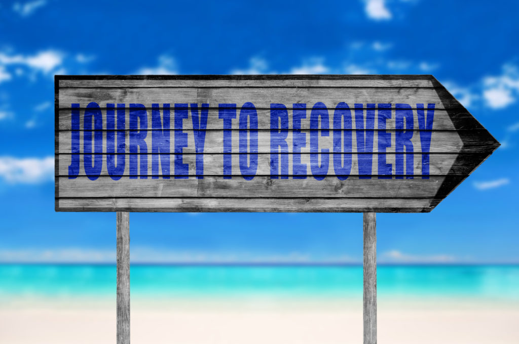 Journey to Recovery wooden sign with on a beach background