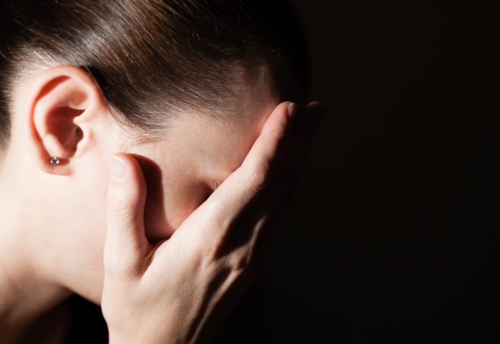 Woman with her hands clasp over face feeling sad.
