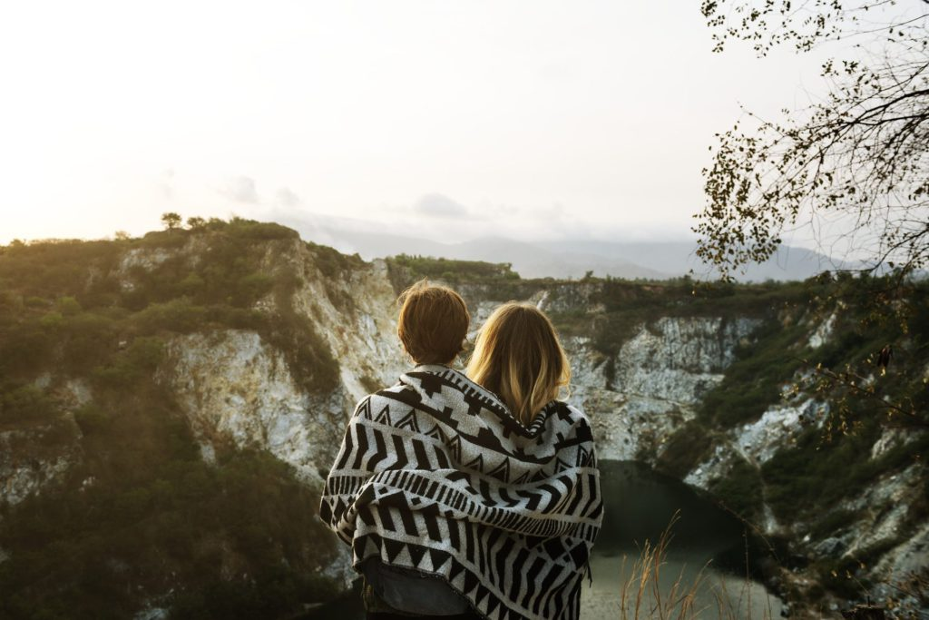 Couple Wrapped in a Blanket staring out at a lake and mountains cropped